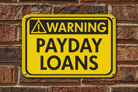 building wall: A yellow warning hanging sign with text Payday Loans on a brick building Stock Photo