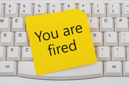unemployed dismissed: A close-up of a keyboard with yellow sticky note with text You are Fired Stock Photo