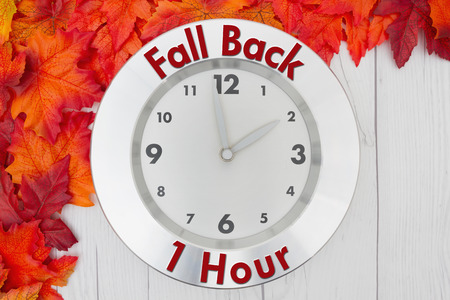 Some fall leaves and a clock on weathered wood with text Fall Back 1 hour