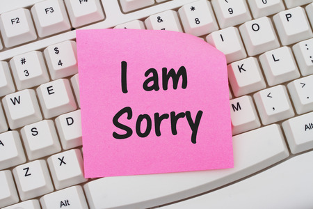 i am sorry: A close-up of a keyboard with pink sticky note with text I am Sorry