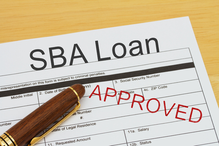 SBA Loan application form with a pen on a desk with an approved stamp Foto de archivo
