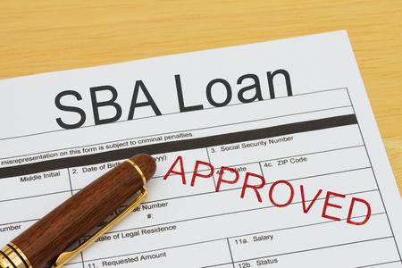 SBA Loan Application Form con una penna su una scrivania con un timbro approvato