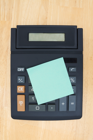 blank spaces: Black calculator with a display on a desk with green sticky note with copy-space for message Stock Photo
