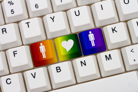 website words: A close-up of a keyboard with rainbow color highlighted symbol of man and a man and heart Stock Photo