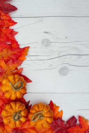 Some fall leaves and pumpkins on weathered wood with copy space for message