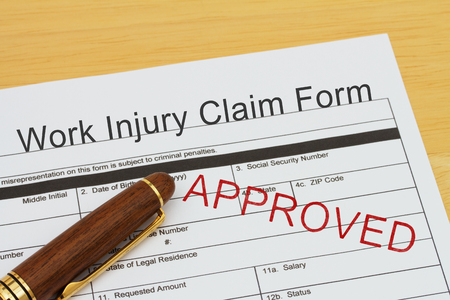 Work Injury Claim Form with a pen on a desk with an approved stamp