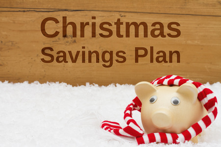 christmas savings: Piggy bank with scarf on snow with a weathered wood background with text Christmas Savings Plan