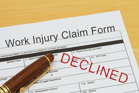 Work Injury Claim Form with a pen on a desk with an declined stamp Banco de Imagens