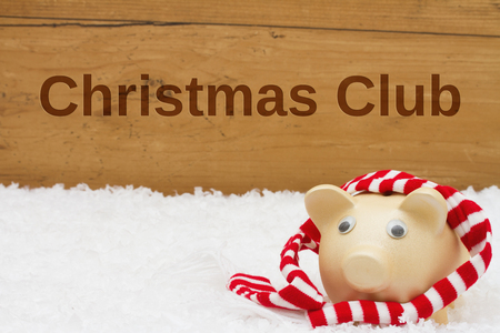 christmas savings: Piggy bank with scarf on snow with a weathered wood background with text Christmas Club