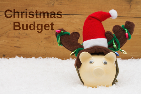 christmas budget: Piggy bank with Christmas hat on snow with a weathered wood background with text Christmas Budget Stock Photo