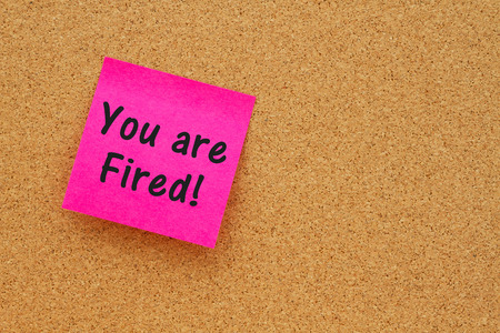 unemployed dismissed: Bulletin board with a pink sticky note with text you are fired