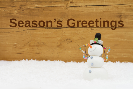 snowman wood: Snowman on snow with weathered wood background with text Seasons Greeting