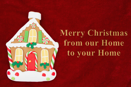 Red plush fabric with a gingerbread house background with text Merry Christmas from our home to your home