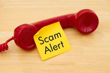 phone receiver: A retro red phone with yellow sticky note on a desk with text Scam Alert