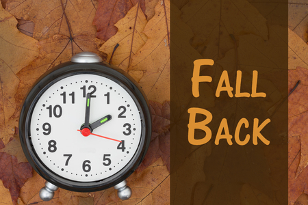 Some fall leaves and retro alarm clock with text Fall Back