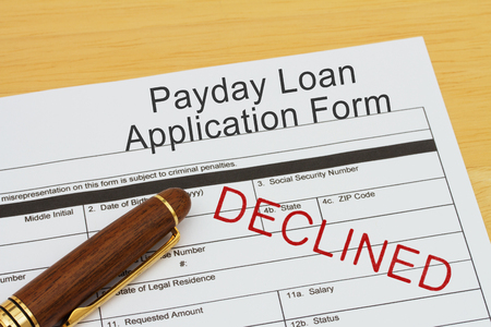 Payday loan application form with a pen on a desk with an declined stamp