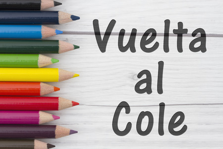 cole: Pencil Crayons with text Vuelta al Cole, Spanish Back to School with weathered wood background