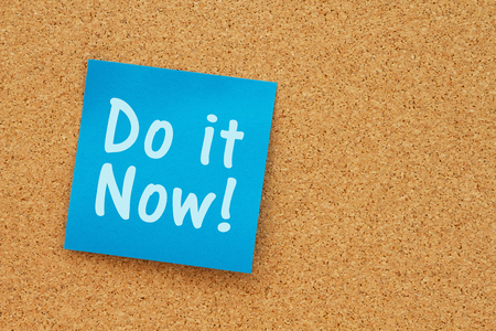 note board: Bulletin board with a blue sticky note with text Do it Now