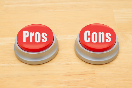 cons: Two red and silver push button on a wooden desk with text Pros and Cons Stock Photo