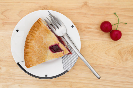 Slice of cherry pie on a plate with a fork and cherries on a wood counter top background