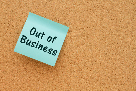note board: Bulletin board with a teal sticky note with text Out of Business Stock Photo