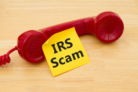 A retro red phone with yellow sticky note on a desk with text IRS Scam Stock Photo
