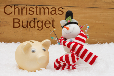 christmas budget: Piggy bank and Snowman with scarf on snow with a weathered wood background with text Christmas Budget