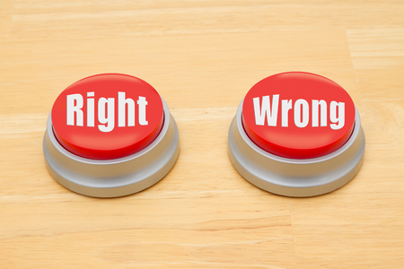 Two red and silver push button on a wooden desk with text Right and Wrong