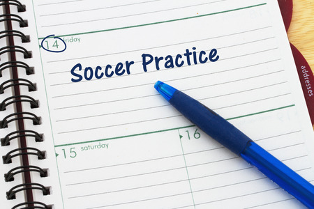 sport object: a day planner with blue pen with text Soccer  Practice Stock Photo