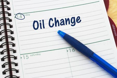 Een dag planner met blauwe pen met tekst Oil Change Stockfoto