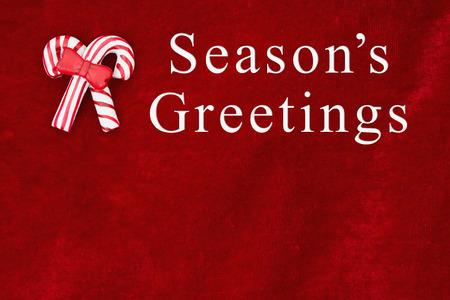 Rode pluche met twee snoep stokken achtergrond met de Groeten van de tekst van het seizoen en de kopie-ruimte voor bericht
