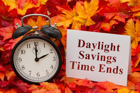 Some fall leaves, black and white alarm clock and a blank greeting card with copy-space Stock Photo