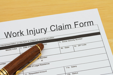 Work Injury Claim Form with a pen on a desk Banco de Imagens