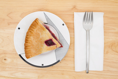 cherry pie: Slice of cherry pie on a plate with a fork on a wood counter top background