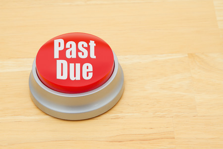 past due: A red and silver push button on a wooden desk with text Past Due
