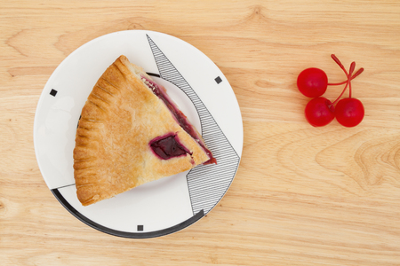 cherry pie: Slice of cherry pie on a plate with cherries on a wood counter top background Stock Photo