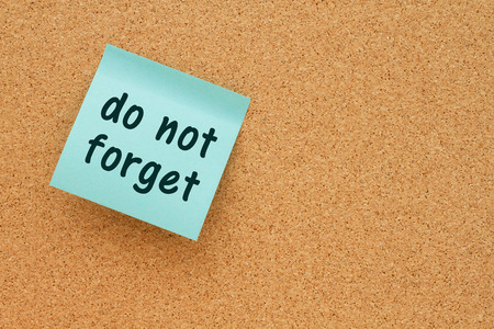 note board: Bulletin board with a teal sticky note with text do not forget Stock Photo