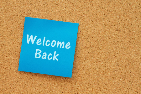 note board: Bulletin board with a blue sticky note with text Welcome Back
