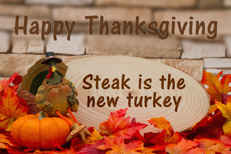 wood plaque: Some fall leaves, turkey on a pumpkin and wood plaque on weathered brick with text Happy Thanksgiving, steak is the new turkey Stock Photo