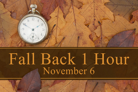 Some fall leaves and retro pocket watch with text Fall Back 1 Hour November 6
