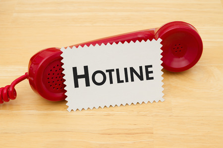 hotline: A retro red phone with note card on a desk with text Hotline