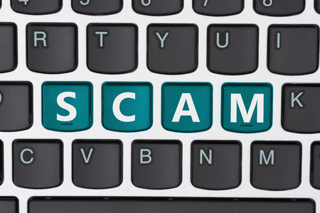web scam: A close-up of a keyboard with teal highlighted text Scam