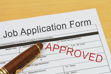 recruit help: Job application form with a pen on a desk with an approved stamp
