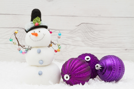 snowman wood: Some snow, Christmas ornaments and a snowman on weathered wood with copy space for message