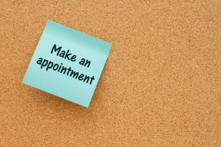 note board: Bulletin board with a blue sticky note with text Make an appointment