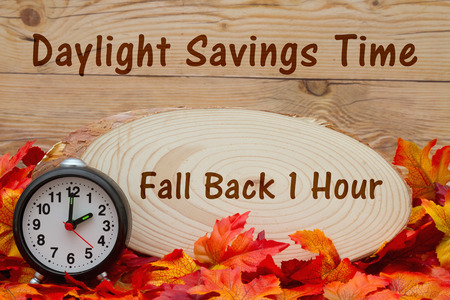 wood plaque: Some fall leaves, an alarm clock and wood plaque on weathered wood with text Fall Back 1 hour