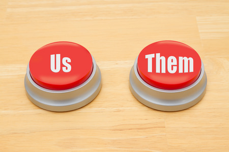 them: Two red and silver push button on a wooden desk with text Us and Them