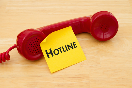 hotline: A retro red phone with yellow sticky note on a desk with text Hotline Stock Photo