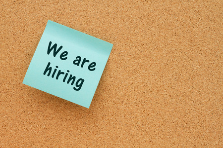 note board: Bulletin board with a blue sticky note with text We are hiring