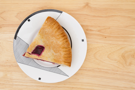 cherry pie: Slice of cherry pie on a plate with a wood counter top background
